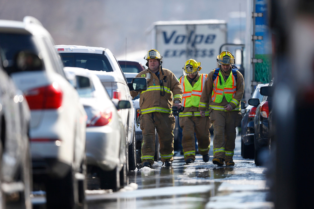 . Firefighters check in on motorist in vehicles are piled up in an accident, Friday, Feb. 14, 2014, in Bensalem, Pa. Traffic accidents involving multiple tractor trailers and dozens of cars have completely blocked one side of the Pennsylvania Turnpike outside Philadelphia and caused some injuries. (AP Photo/Matt Rourke)
