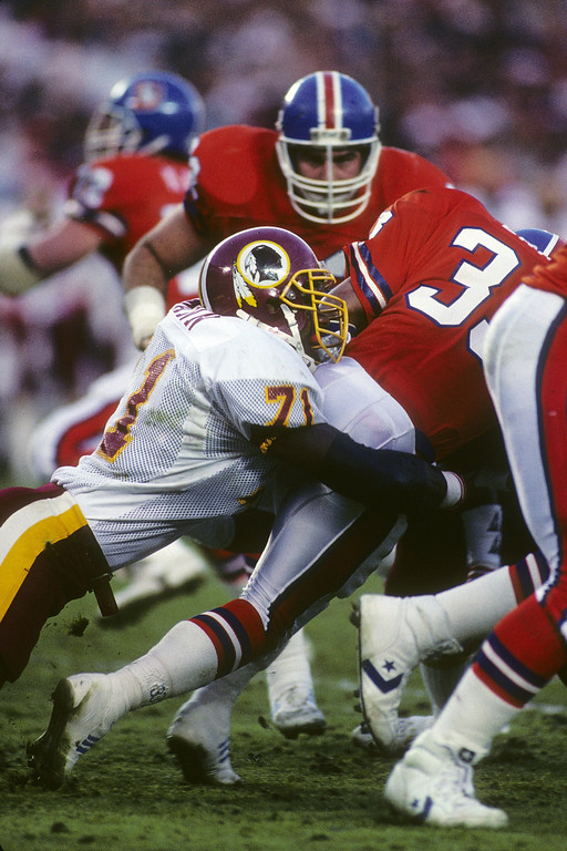 . Defensive end Charles Mann #71 of the Washington Redskins tackles running back Gene Lang #30 of the Denver Broncos during Super Bowl XXII at Jack Murphy Stadium on January 31, 1988 in San Diego, California.    (Photo by George Rose/Getty Images)