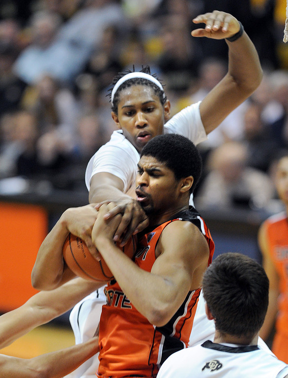 . Xavier Johnson of Colorado reaches over trying to knock the ball from Devon Collier of Oregon State during the second half of the March 9, 2013 game in Boulder.    (Cliff Grassmick/Boulder Daily Camera)