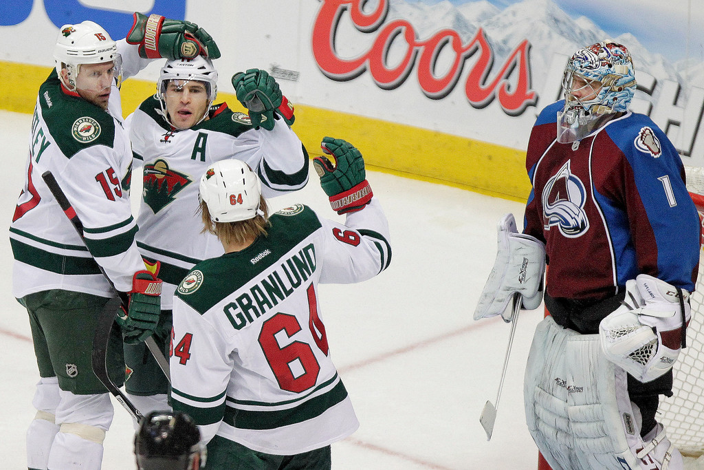 . Minnesota Wild\'s Zach Parise, second from left, gets hugged by teammates Dany Heatley, left, and Mikael Granlund, of Finland, after scoring a goal on Colorado Avalanche goalie Semyon Varlamov, right, of Russia, during the first period of an NHL hockey game Thursday, Jan. 30, 2014, in Denver. (AP Photo/Barry Gutierrez)