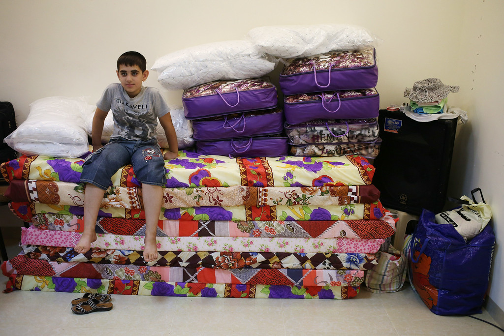 . A displaced Iraqi Christian boy who fled from the Christian village of Hamdania near Mosul province in Iraq, sits on a pile of mattress where he settled with his family at a church hall that turned for the displaced Christian families, in Ainkawa, a suburb of Irbil, with a majority Christian population, Iraq, Friday, June 27, 2014. Around 2,000 Christians had entered the Kurdish city of Irbil by Thursday morning, June 26. A Christian official there said the Kurdish region is the only part of Iraq where Christians are protected from violence. (AP Photo/Hussein Malla)