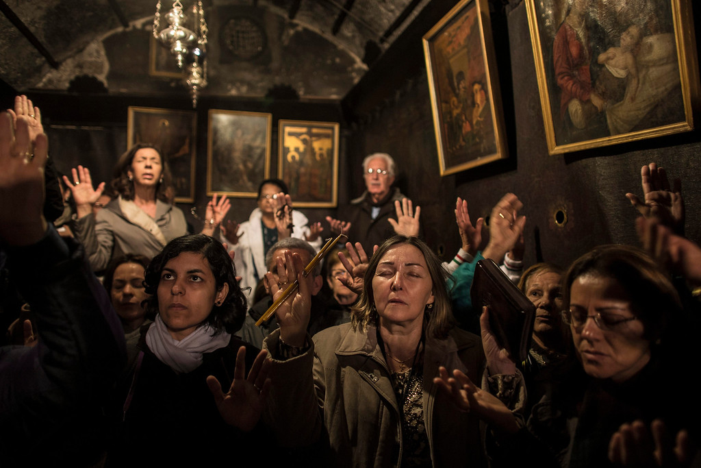 . Pilgrims pray inside the Grotto where Christians believe the Virgin Mary gave birth to Jesus Christ in the Church of the Nativity, in the West Bank town of Bethlehem on Christmas Eve, 24 December 2013.  EPA/OLIVER WEIKEN