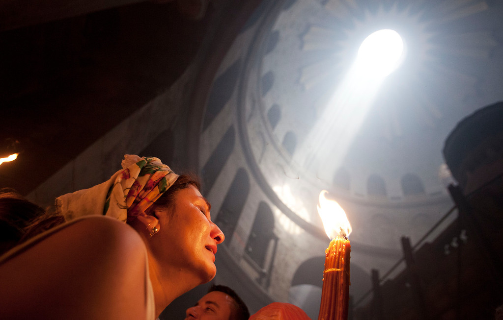 ". A Christian pilgrim holds candles at the church of the Holy Sepulcher, traditionally believed to be the burial site of Jesus Christ, during the ceremony of the Holy Fire in Jerusalem\'s Old City, Saturday, April 19, 2014. The ""holy fire\"" was passed among worshippers outside the Church and then taken to the Church of the Nativity in the West Bank town of Bethlehem, where tradition holds Jesus was born, and from there to other Christian communities in Israel and the West Bank. (AP Photo/Dan Balilty)"