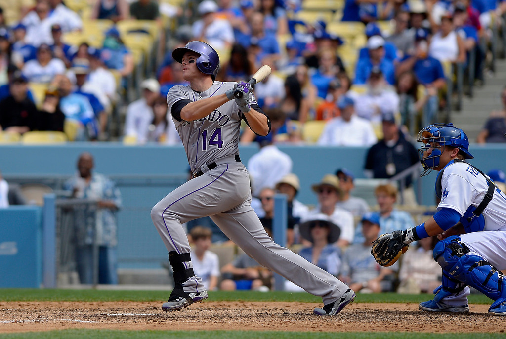 . Colorado Rockies\' Josh Rutledge, left, hits a three-run home run as Los Angeles Dodgers catcher Tim Federowicz looks on during the sixth inning of a baseball game, Sunday, April 27, 2014, in Los Angeles. (AP Photo/Mark J. Terrill)