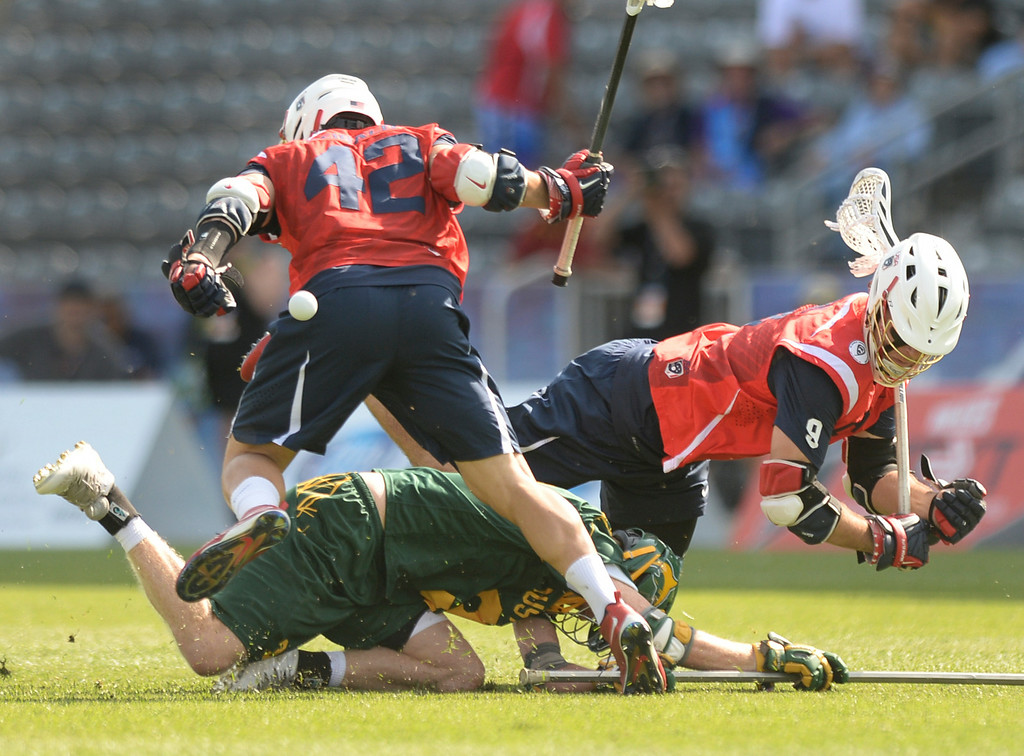 . COMMERCE CITY, CO - JULY 17: Australia defender Brad Sheldon (3) knocked the ball away from Americans Max Seibald (42) and Garrett Thul (8) in the first half. Team USA faced Australia in a FIL World Championship semifinal game Thursday night, July 17, 2014.  Photo by Karl Gehring/The Denver Post