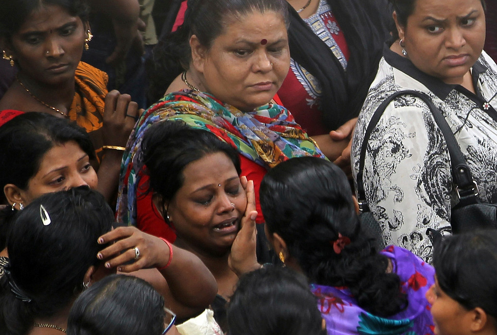 . A woman cries for her missing relative as others gather near the site of a building that collapsed in Mumbai, India, Friday, Sept. 27, 2013.  (AP Photo/Rajanish Kakade)