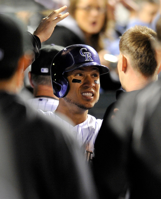 . Colorado Rockies\' Carlos Gonzalez is congratulated by teammates after scoring against the San Diego Padres during the fifth inning of a baseball game on Saturday, April 6, 2013, in Denver. (AP Photo/Jack Dempsey)