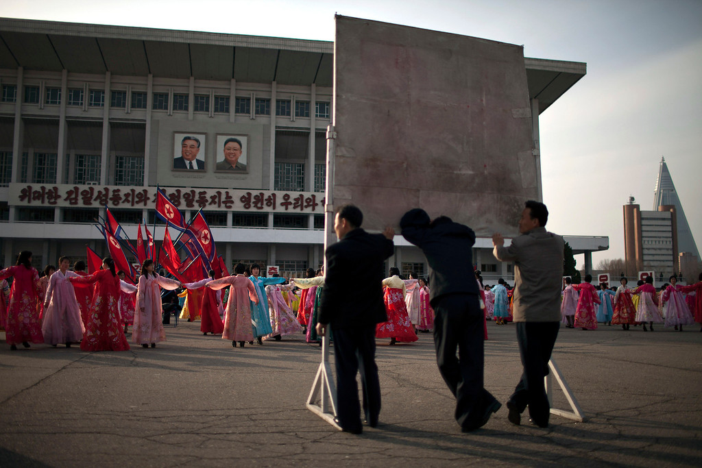 . Men support a signboard while watching a mass folk dance in front of the Pyongyang Indoor Stadium in Pyongyang, North Korea, Monday, April 15, 2013. Oblivious to international tensions over a possible North Korean missile launch, Pyongyang residents spilled into the streets Monday to celebrate a major national holiday, the birthday of their first leader, Kim Il Sung. (AP Photo/Alexander F. Yuan)
