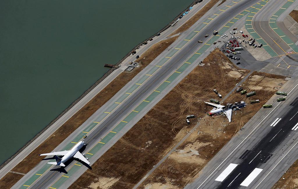 . This aerial photo shows the crash site of Asiana Flight 214, right, at the San Francisco International Airport in San Francisco, Saturday,  July 6, 2013.  (AP Photo/Marcio Jose Sanchez)