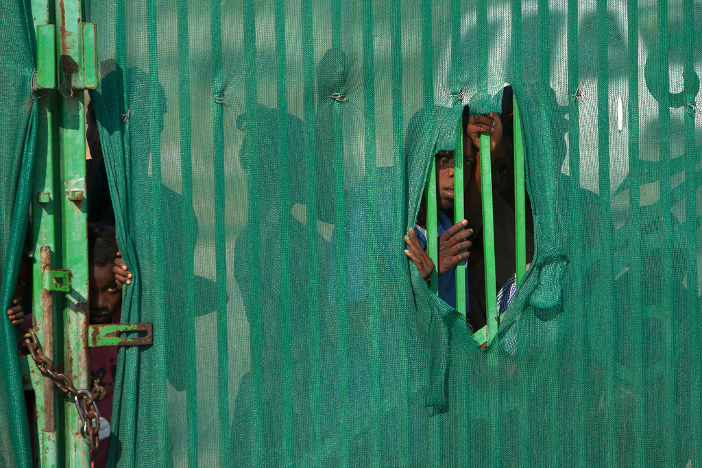 . Children peer from behind a fence during a Christmas gift distribution event at the national palace in Port-au-Prince, Haiti, Wednesday Dec. 19, 2012.  (AP Photo/Dieu Nalio Chery)