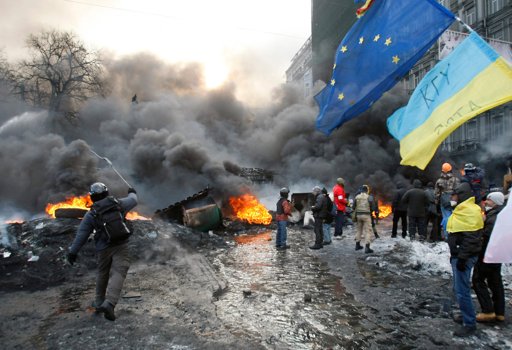 . A protester throws stone during clashes, in central Kiev, Ukraine, Thursday Jan. 23, 2014. Thick black smoke from burning tires engulfed parts of downtown Kiev as an ultimatum issued by the opposition to the president to call early election or face street rage was set to expire with no sign of a compromise on Thursday. (AP Photo/Darko Vojinovic)