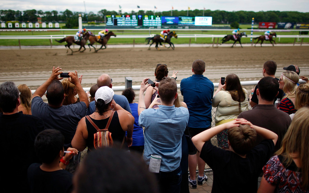 . Race fans react during a pre race, ahead of the 145th running of the Belmont Stakes, the final leg of horse racing\'s triple crown, at Belmont Park in Elmont, New York, June 8, 2013.  REUTERS/Chip East