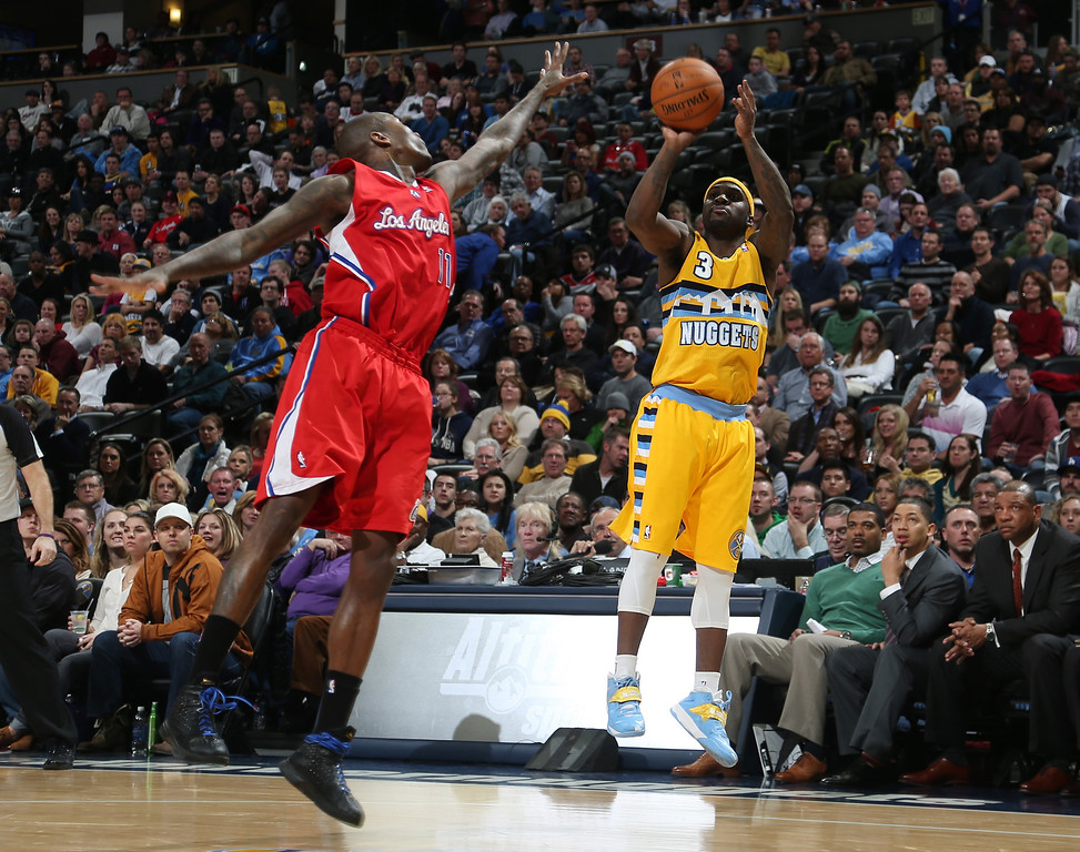 . Denver Nuggets guard Ty Lawson, right, goes up for shot over Los Angeles Clippers guard Jamal Crawford in the fourth quarter of the Nuggets\' 116-115 victory in an NBA basketball game in Denver, Monday, Feb. 3, 2014. (AP Photo/David Zalubowski)