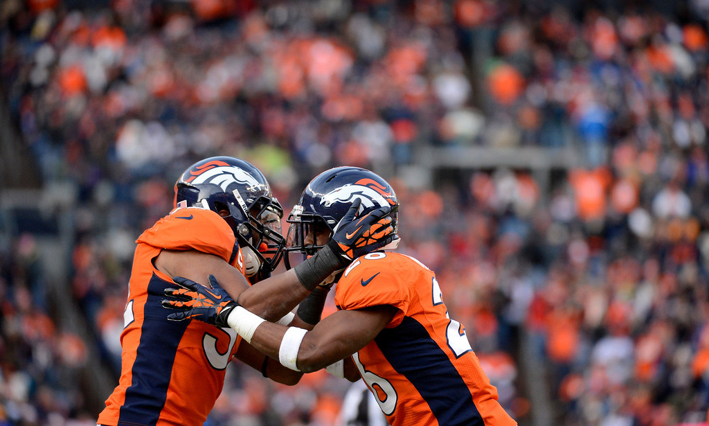 . Denver Broncos free safety Rahim Moore (26) and Denver Broncos outside linebacker Wesley Woodyard (52) celebrate sacking Kansas City Chiefs quarterback Brady Quinn (9) during the second quarter. The Denver Broncos vs Kansas City Chiefs at Sports Authority Field Sunday December 30, 2012. Joe Amon, The Denver Post
