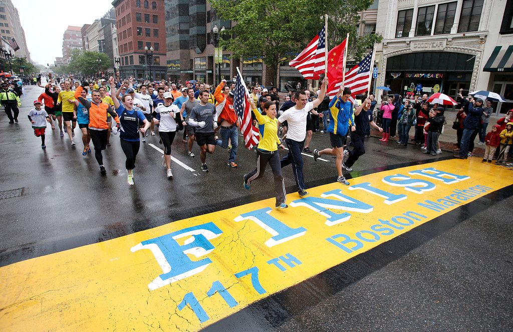 . Runners who were unable to finish the Boston Marathon on April 15 because of the bombings cross the finish line on Boylston Street after the city allowed them to finish the last mile of the race in Boston, Saturday, May 25, 2013. (AP Photo/Winslow Townson)