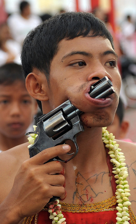 . A devotee of the Chinese Bang Neow Shrine parades with a gun piercing his cheek during a street procession to mark the annual Vegetarian Festival in the southern Thai town of Phuket on October 2, 2011.  During the festival, which begins on the first evening of the ninth lunar month and lasts nine days, religious devotees slash themselves with swords, pierce their cheeks with sharp objects and commit other painful acts to purify themselves, taking on the sins of the community.    AFP PHOTO/Christophe ARCHAMBAULT