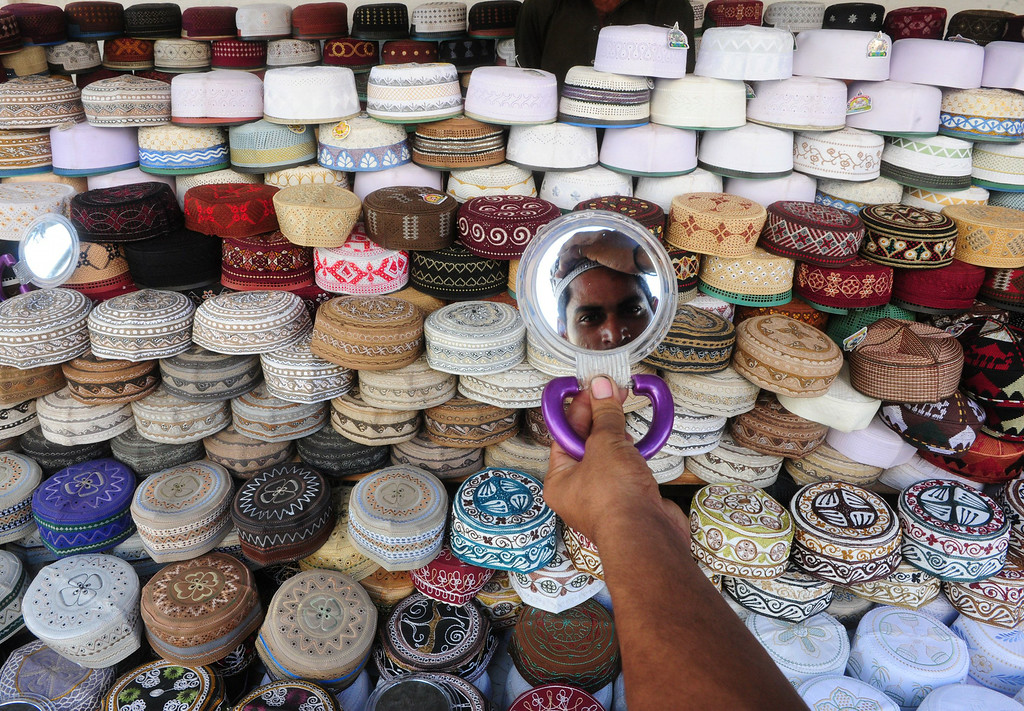 . A Pakistani resident tries on a cap at a stall ahead of the Islamic holy month of Ramadan in Karachi on June 28, 2014. Muslims are preparing for Islam\'s holy month of Ramadan, which is calculated on the sighting of the new moon, and during which they fast from dawn until dusk. ASIF HASSAN/AFP/Getty Images
