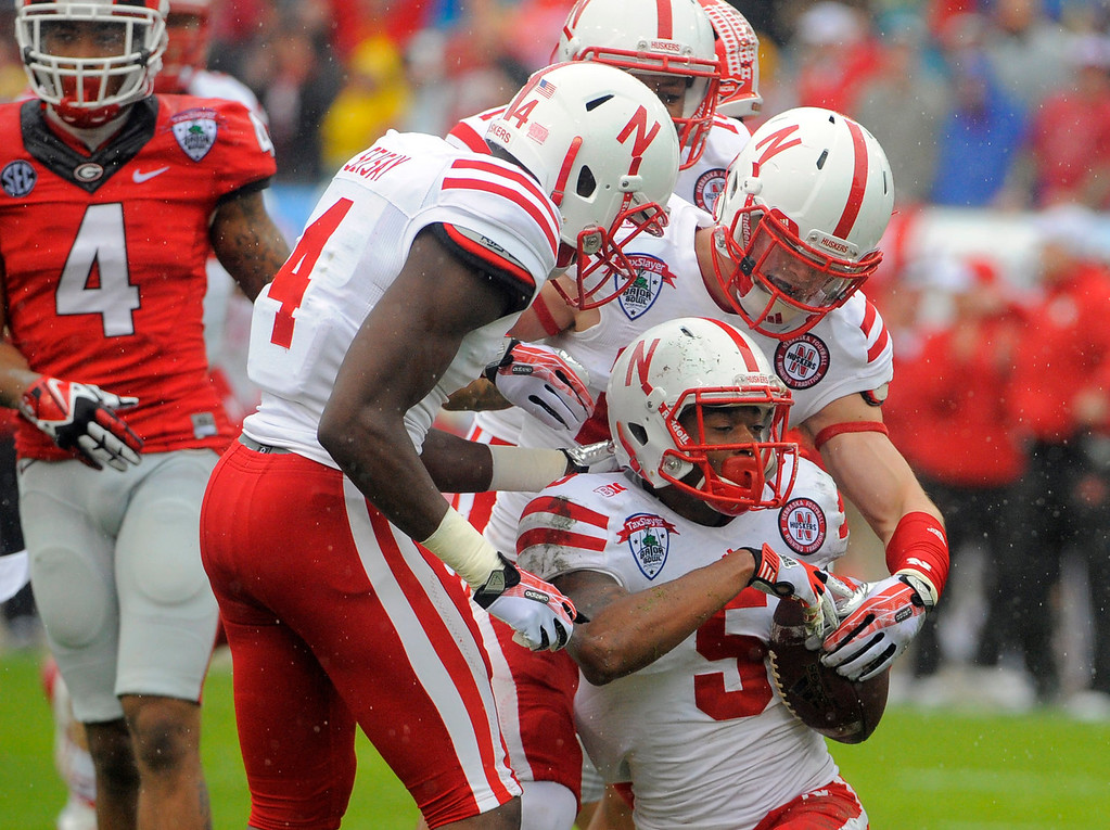 . Nebraska cornerback Josh Mitchell (5) celebrates with his teammates after recovering a fumbled kick return during the first half of the Gator Bowl NCAA college football game against Georgia, Wednesday, Jan. 1, 2014, in Jacksonville, Fla. (AP Photo/Stephen B. Morton)
