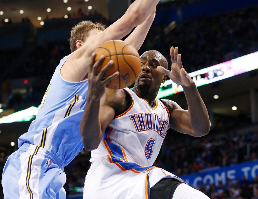 . Oklahoma City Thunder forward Serge Ibaka (9) drives under the basket past Denver Nuggets center Timofey Mozqov (25) in the third quarter of an NBA basketball game in Oklahoma City, Monday, March 24, 2014. Oklahoma City won 117-96. (AP Photo/Sue Ogrocki)