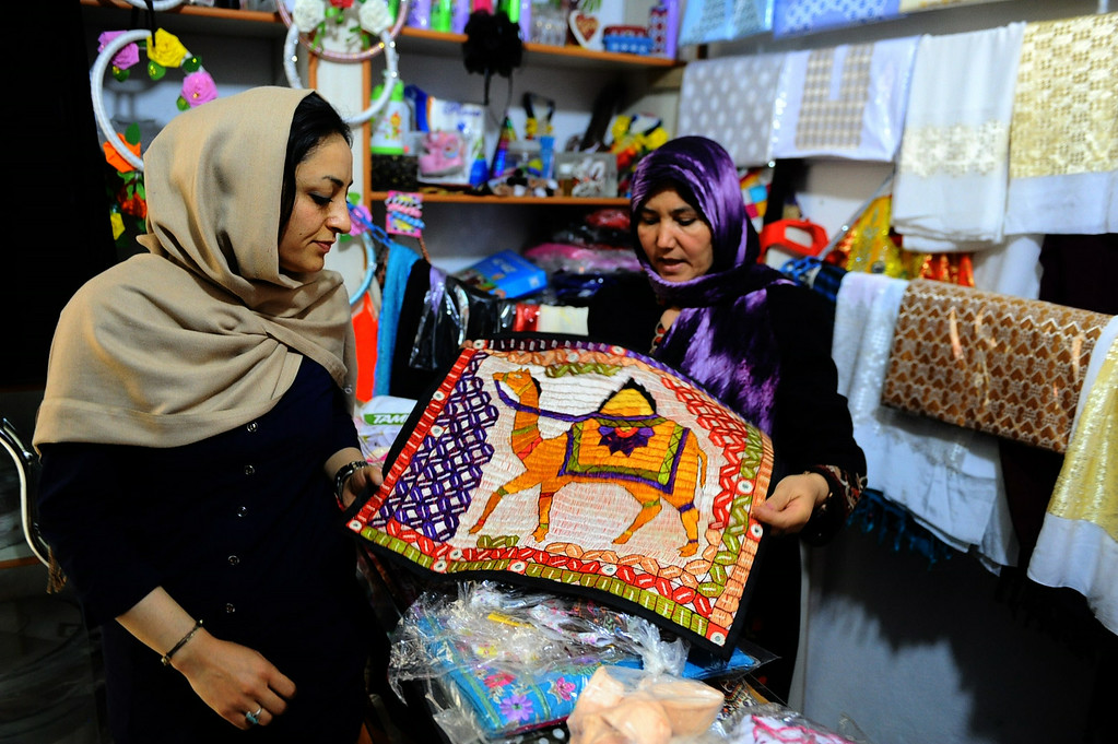 . In this picture taken on June 2, 2014, Afghan shoppers examine a silk cloth to buy in a women\'s business centre in the city of Herat province.  AFP PHOTO/Aref Karimi/AFP/Getty Images