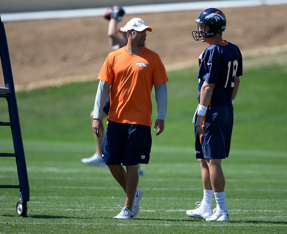 . Denver Broncos offensive coordinator talks with Denver Broncos quarterback Peyton Manning (18) during practice August 25, 2014 at Dove Valley.(Photo by John Leyba/The Denver Post)