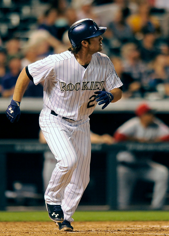 . Colorado Rockies Charlie Culberson watches his three-run home run sail over the wall in the fifth inning of a baseball game against the Cincinnati Reds on Thursday, Aug. 14, 2014, in Denver. (AP Photo/Chris Schneider)