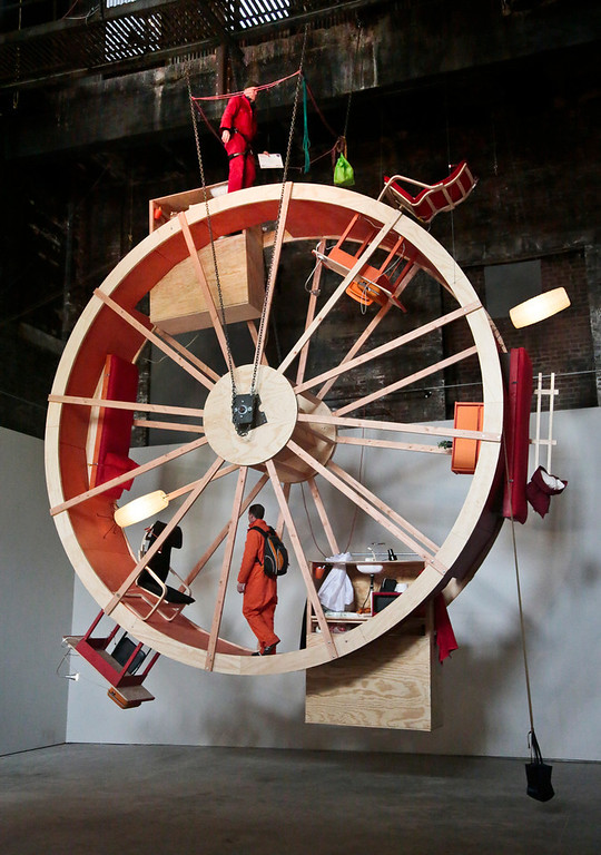 """. The performance art \""""In Orbit,\"""" a 25-foot wheel made from wood, steel, and furniture, is home for artists Ward Shelley, top, and Alex Schweder, bottom, for 10 days at the Boiler gallery in the Brooklyn borough of New York, Tuesday, March 4, 2014. They will share two living units arrayed over the hamster-wheel-like sculpture, with Shelly living on the outside and Schweder on the inside. The structure will remain on view through April 5.  (AP Photo/Bebeto Matthews)"""