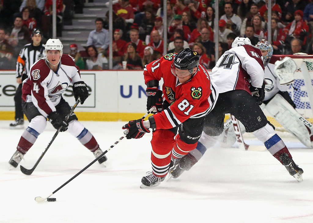 . Marian Hossa #81 of the Chicago Blackhawks controls the puck between Tyson Barrie #4 (L) and Ryan Wilson #44 of the Colorado Avalanche at the United Center on January 14, 2014  in Chicago, Illinois. (Photo by Jonathan Daniel/Getty Images)