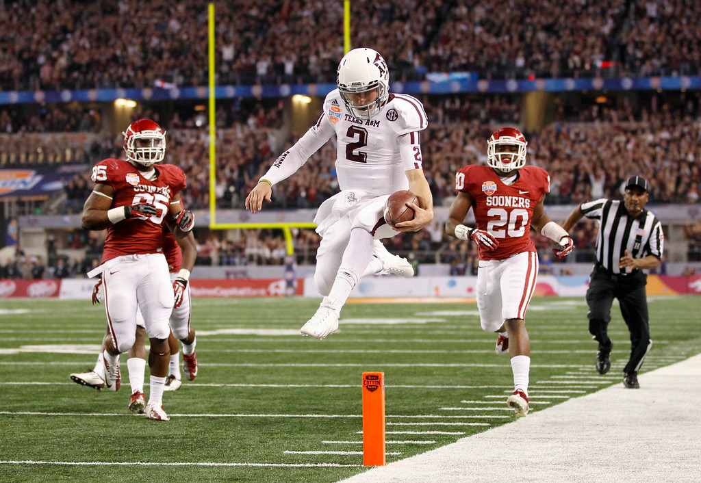 . Texas A&M quarterback Johnny Manziel runs for a touchdown as University of Oklahoma defensive end Geneo Grissom (85) and linebacker Frank Shannon (20) pursue during the first half of the Cotton Bowl Classic NCAA football game played at Cowboys Stadium in Arlington, Texas January 4, 2013. REUTERS/Mike Stone