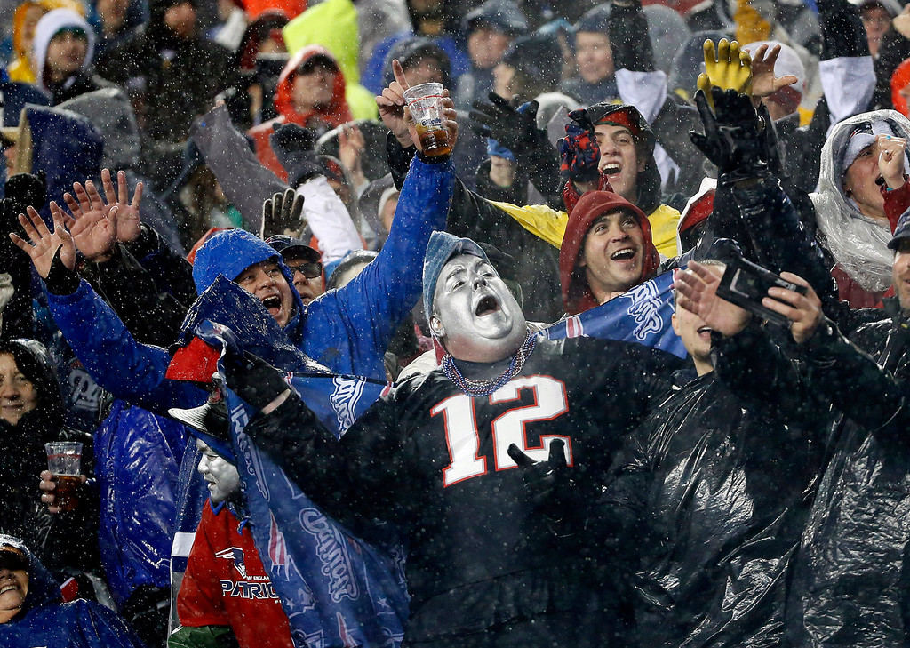 . Rain-soaked New England Patriots fans cheer during the third quarter of an NFL football game between the Patriots and the Buffalo Bills, Sunday, Dec. 29, 2013, in Foxborough, Mass. The Patriots won 34-20, and will have a first-round bye in the AFC playoffs. (AP Photo/Elise Amendola)