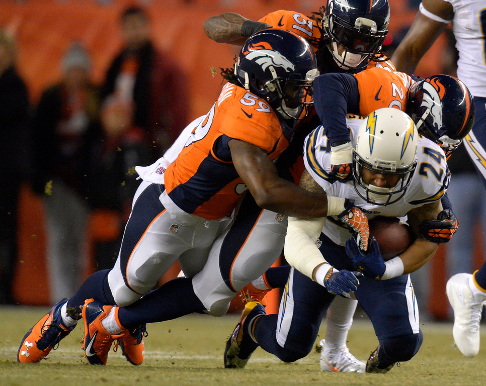 . DENVER, CO - DECEMBER 12: Denver Broncos outside linebacker Danny Trevathan (59), strong safety Mike Adams (20) and cornerback Omar Bolden (31) tackle San Diego Chargers running back Ryan Mathews (24) during the first quarter. The Denver Broncos vs. the San Diego Chargers at Sports Authority Field at Mile High in Denver on December 12, 2013. (Photo by John Leyba/The Denver Post)