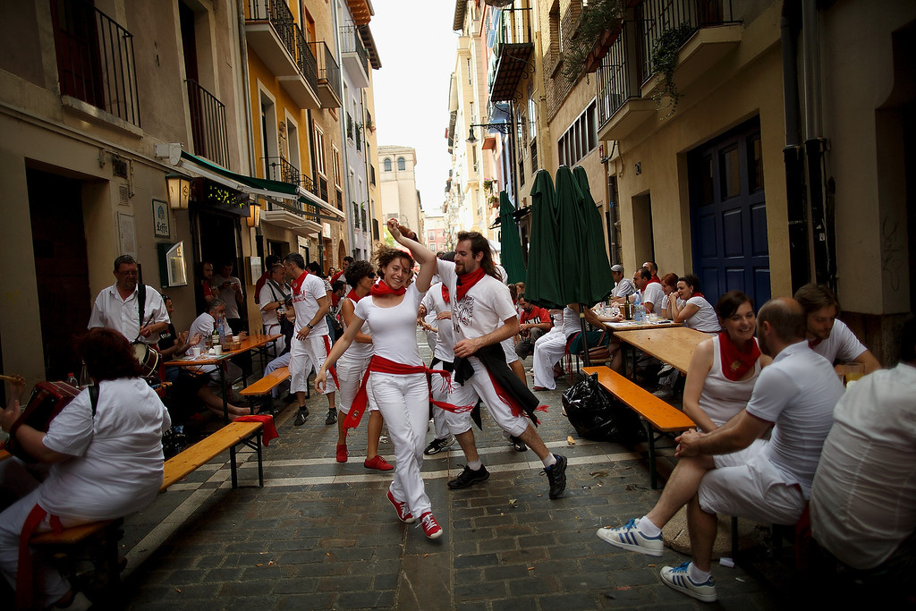 . PAMPLONA, SPAIN - JULY 10:  Revellers dance while musicians from Oberena play traditional Basque Country music in the street after having lunch on the fifth day of the San Fermin Running Of The Bulls festival on July 10, 2013 in Pamplona, Spain. The annual Fiesta de San Fermin, made famous by the 1926 novel of US writer Ernest Hemmingway \'The Sun Also Rises\', involves the running of the bulls through the historic heart of Pamplona, this year for nine days from July 6-14.  (Photo by Pablo Blazquez Dominguez/Getty Images)