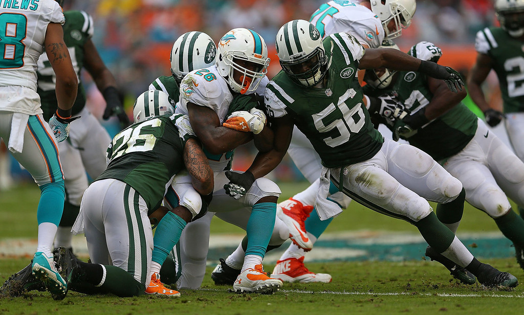 . Lamar Miller #26 of the Miami Dolphins rushes during a game against the New York Jets at Sun Life Stadium on December 29, 2013 in Miami Gardens, Florida.  (Photo by Mike Ehrmann/Getty Images)