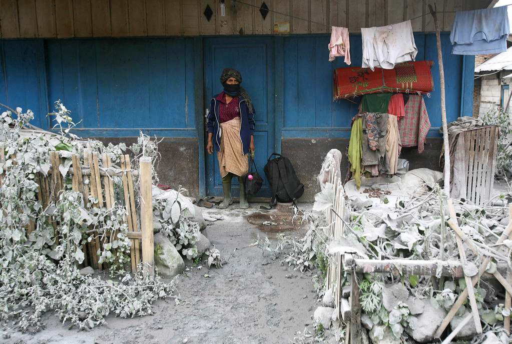 . A woman stands outside her house as her front yard is covered with volcanic ash from the eruption of Mount Sinabung, in Mardingding, North Sumatra, Indonesia, Tuesday, Nov. 5, 2013. The 2,600-meter (8,530-foot) -high volcano has been erupting since Sunday, unleashing volcanic ash high into the sky and forcing the evacuation of villagers living around its slope. (AP Photo/Binsar Bakkara)