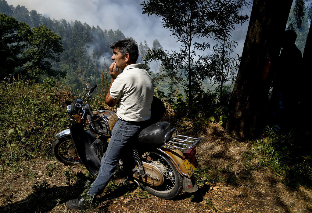 . A man sitting in a motorbike watches a wildfire burn around Caramulo, central Portugal, on August 30, 2013.  AFP PHOTO / PATRICIA DE MELO MOREIRA/AFP/Getty Images