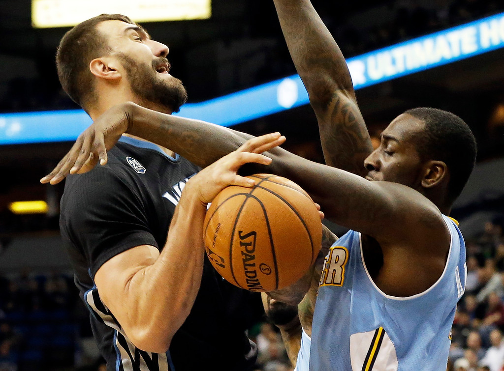 . Minnesota Timberwolves\' Nikola Pekovic, left, of Montenegro, gets tied up during a shot-attempt by Denver Nuggets\'s J.J. Hickson in the first quarter of an NBA basketball game on Wednesday, Nov. 27, 2013, in Minneapolis. (AP Photo/Jim Mone)
