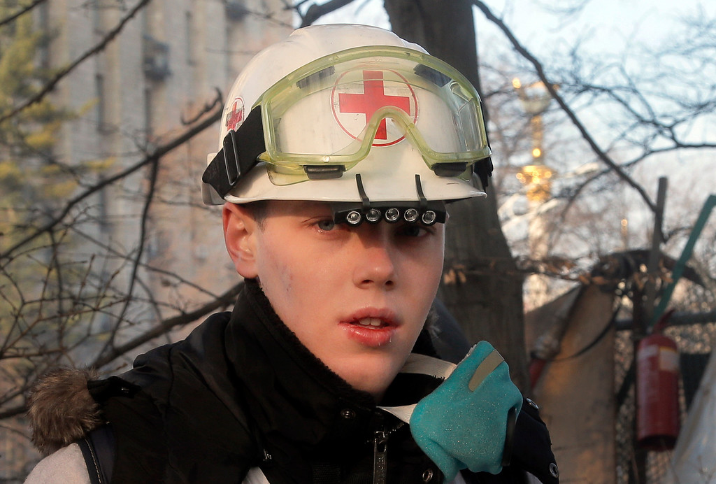 . An opposition supporter and medical volunteer stands at a barricade near the Presidential office in Kiev, Ukraine, Friday, Feb. 21, 2014.  (AP Photo/Efrem Lukatsky)