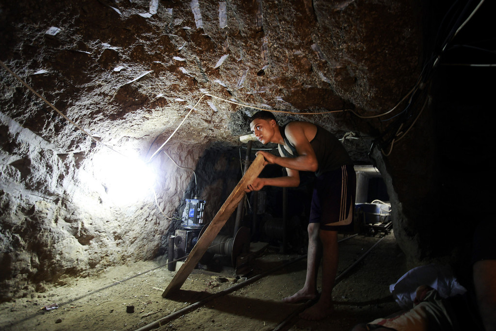 . In this Monday, Sept. 30, 2013 photo, a Palestinian man works in a tunnel in Rafah, on the border between Egypt and the southern Gaza Strip. Since the summer, Egyptís military has tried to destroy or seal off most of the smuggling tunnels under the Gaza-Egypt border, a consequence of the heightened tensions between Cairo and the Hamas government in Gaza. The tunnels once employed thousands of young men in Gaza. By early September, with most tunnels closed, only few tunnel workers reported to their jobs for maintenance work. Some mask their faces with shirts to avoid identification while working, for fear of repercussions in case they were to travel to Egypt in the future. (AP Photo/Hatem Moussa)