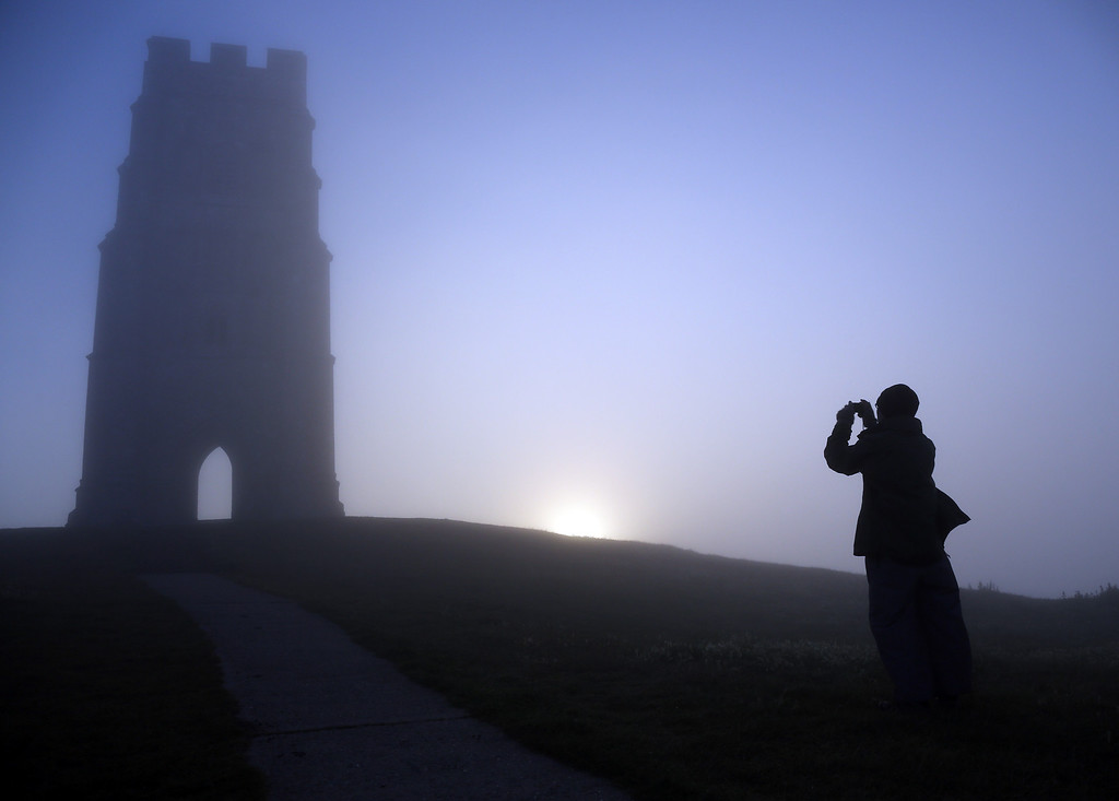 . A visitor to Glastonbury Tor takes a photograph of St. Michael\'s Tower, a ruined 14th-century church tower, as the rising sun begins to clear the early morning mist and fog near the town of Glastonbury on September 4, 2013 in Somerset, England. Parts of the UK are set to enjoy a late summer heatwave today, with temperatures possibly reaching 28C in central, eastern and southern England, with temperatures predicted to climb even higher tomorrow.  (Photo by Matt Cardy/Getty Images)