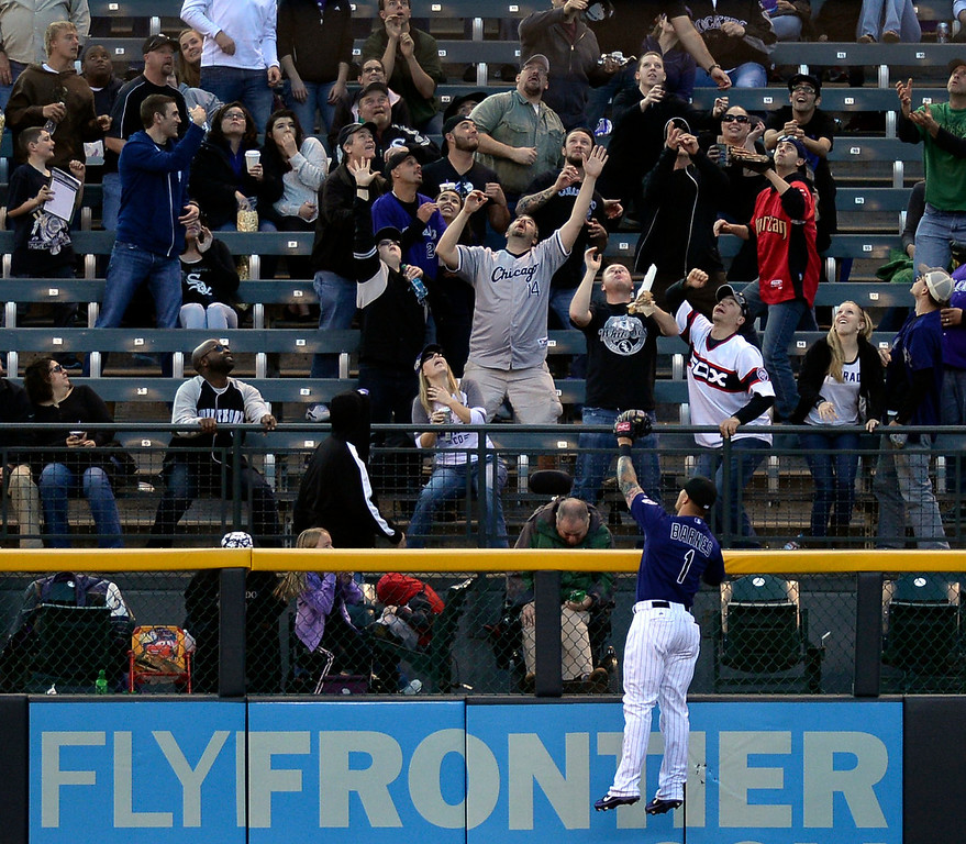 . Fans in left field scrambled for a home run ball off the bat of Chicago slugger Avisail Garcia in the second inning. The Chicago White Sox clobbered the Colorado Rockies 15-3 Tuesday night, April 8, 2014 at Coors Field in Denver.  (Photo by Karl Gehring/The Denver Post)