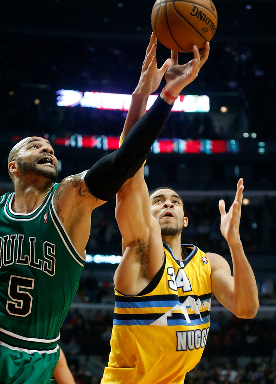 . Chicago Bulls forward Carlos Boozer (5) battles Denver Nuggets center JaVale McGee for a loose ball during the first half of an NBA basketball game, Monday, March 18, 2013, in Chicago. (AP Photo/Charles Rex Arbogast)