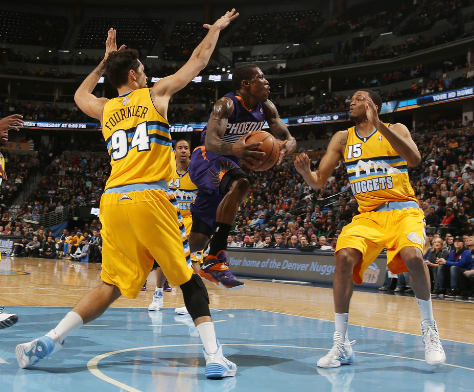 . Phoenix Suns guard Eric Bledsoe, center, drives the lane for a shot between Denver Nuggets guard Evan Forunier, left, of France, and forward Anthony Randolph in the first quarter of an NBA basketball game in Denver on Friday, Dec. 20, 2013. (AP Photo/David Zalubowski)