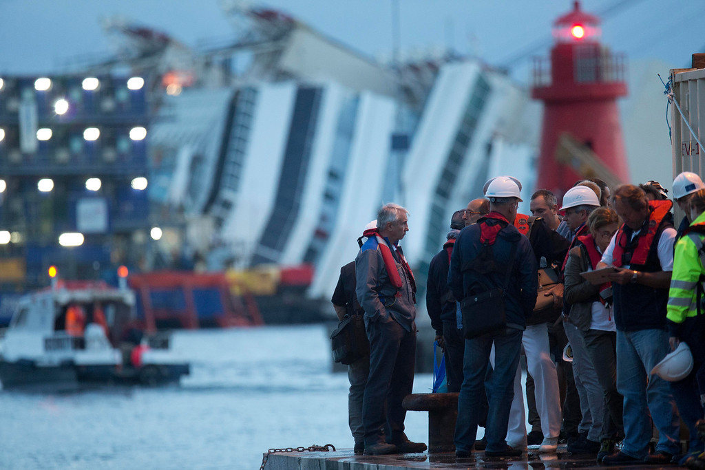 . Workers stand in front of the Costa Concordia ship lying on its side on the Tuscan Island of Giglio, Italy, early Monday morning, Sept. 16, 2013. An international team of engineers is trying a never-before attempted strategy to set upright the luxury liner, which capsized after striking a reef in 2012 killing 32 people. (AP Photo/Andrew Medichini)