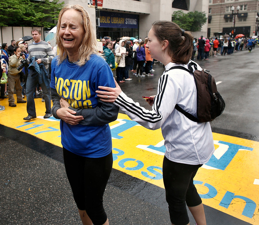 . Pam Vingsness, right, comforts her crying mother, Rachel, of Newton, Mass., after they crossed the finish line, as runners who were unable to finish the Boston Marathon on April 15 because of the bombings were allowed to finish the last mile of the race in Boston, Saturday, May 25, 2013. (AP Photo/Winslow Townson)