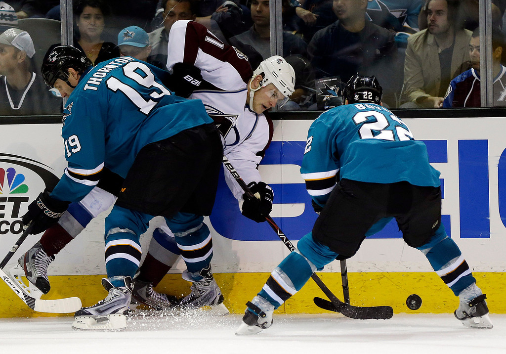 . Colorado Avalanche\'s Jamie McGinn, center, is pressed against the boards by San Jose Sharks\' Joe Thornton (19) and Dan Boyle, right, during the second period of an NHL hockey game on Friday, April 11, 2014, in San Jose, Calif. (AP Photo/Marcio Jose Sanchez)