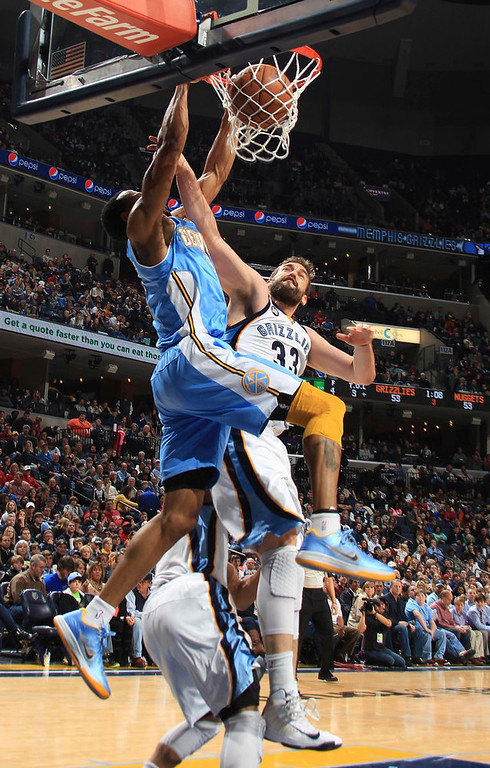 . Denver Nuggets forward Andre Iguodala (L) dunks over Memphis Grizzlies center Marc Gasol (33), of Spain, during the second half of their NBA basketball game in Memphis, Tennessee December 29, 2012. The Grizzlies defeated the Nuggets 81-72.   REUTERS/Nikki Boertman
