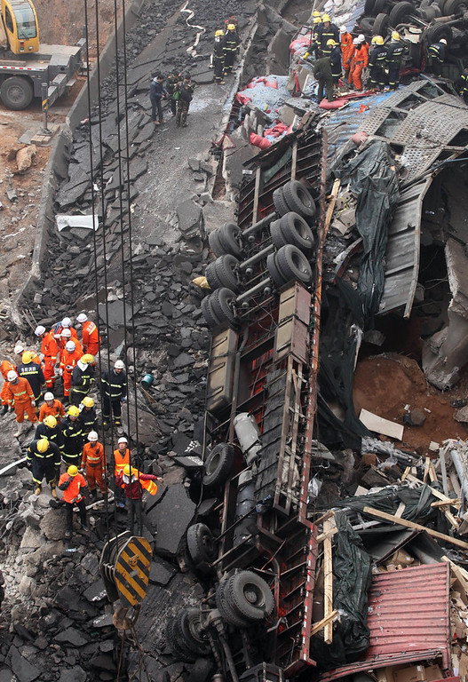 . Rescuers work at the scene of the collapsed Yichang bridge near the city of Sanmenxia, central China\'s Henan province, on February 1, 2013 after a fireworks-laden truck exploded as it crossed the bridge killing 26 people as the structure collapsed and vehicles plummeted to the ground, state-run media reported. An 80-meter long part of the bridge collapsed and six vehicles had been retrieved from the debris, China\'s official news agency Xinhua said. The bridge near the city of Sanmenxia is on the G30 expressway, the longest road in China, which stretches for nearly 4,400 kilometers (2,700 miles) from China\'s western border with Kazakhstan to the eastern Yellow Sea. AFP PHOTO STR/AFP/Getty Images