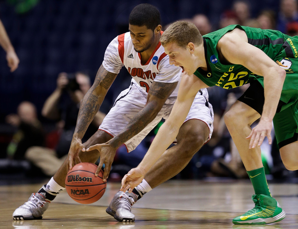 . Louisville forward Chane Behanan and Oregon forward E.J. Singler (25) battle for a loose ball during the first half of a regional semifinal in the NCAA college basketball tournament, Friday, March 29, 2013, in Indianapolis. (AP Photo/Darron Cummings)