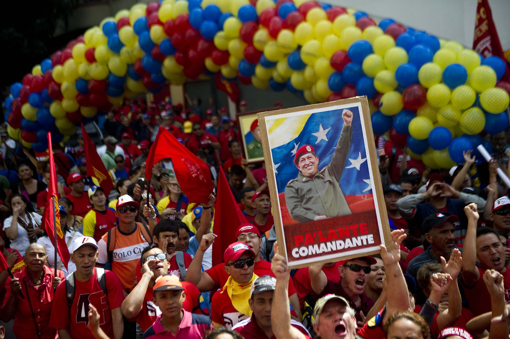 . Supporters of Venezuelan President Nicolas Maduro show a portrait of late President Hugo Chavez when they gather in front of the Congress before the inauguration ceremony of Maduro, in Caracas on April 19, 2013.  RAUL ARBOLEDA/AFP/Getty Images