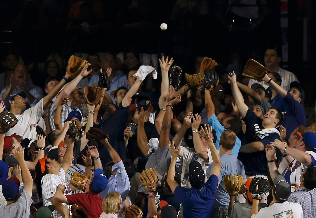 . Fans reach up to catch a home run ball off the bat of National League batter David Wright, of the New York Mets, during the Major League Baseball All-Star Game Home Run Derby in New York, July 15, 2013. REUTERS/Mike Segar